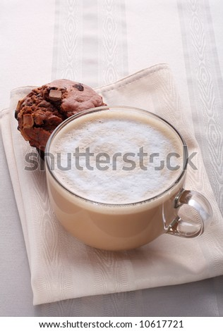 large cup of fresh coffee latte cappucino and chocolate muffin on the tea-towels - stock photo