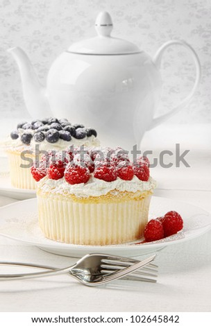 Large cupcakes with raspberries and cream on table
