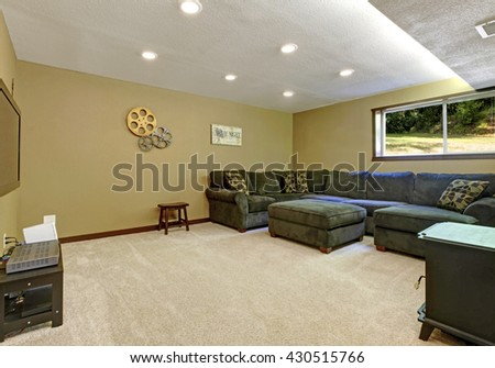 Large day light open basement with green sofa, stove and TV. - stock photo