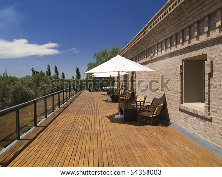Large deck balcony. Chairs, tables and umbrellas under the sun. - stock photo