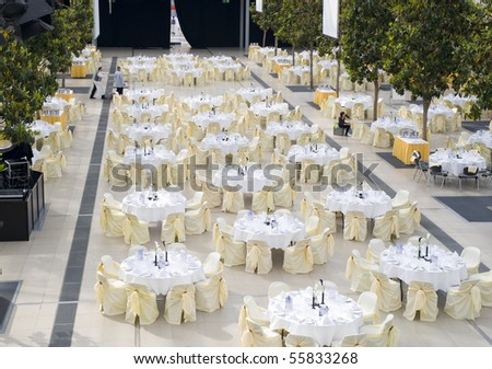 Large dining table set for wedding, dinner or another corporate event with beautiful decoration between green trees inside with people moving blurred - stock photo