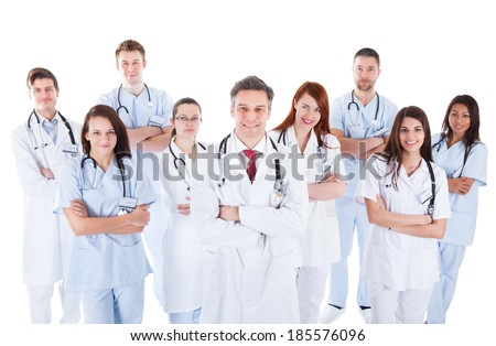Large diverse group of medical staff in white uniforms standing grouped behind a handsome middle-aged bearded doctor or physician isolated on white - stock photo