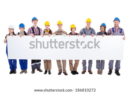 Large diverse multiethnic group of workmen and women standing in a line holding a long blank white banner with copyspace for your text isolated on white - stock photo