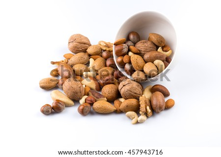 Large diversity of healthy nuts in a white bowl - isolated
