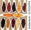 Large dried fruit selection in white porcelain dishes over woven wicker background. - stock photo