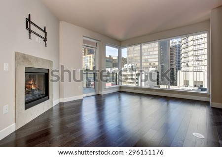 Large empty living room with fireplace and hardwood floor. - stock photo
