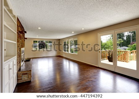 Large empty living room with fireplace and hardwood floor.