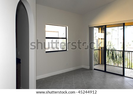 large empty room with arched doorway, window, and sliding glass doors - stock photo