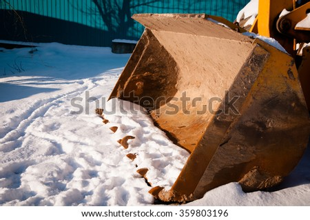 Large excavator bucket on ground covered with snow on a sunny day - stock photo