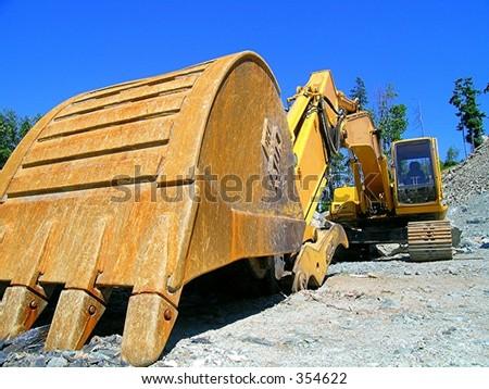 Large Excavator taking a break from devastating a rural hillside - stock photo