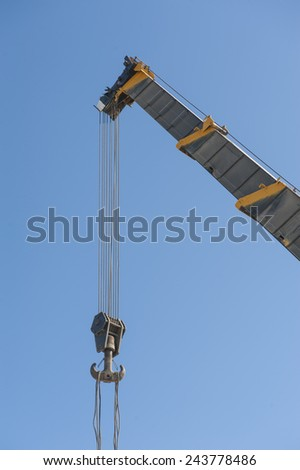 Large extended industrial crane jib boom arm against a blue sky background