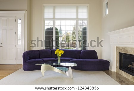 Large family living room with suede sofa, glass table in front of large double pane window with daylight coming in to room - stock photo