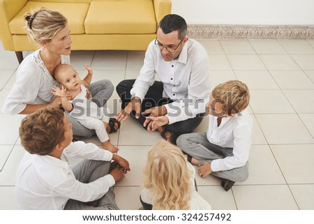 Large family playing together when sitting on the floor