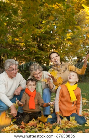 large family plays in the autumn park