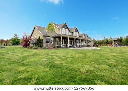 Large farm country house with spring green landscape, kids play ground. - stock photo