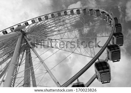 Large ferris wheel against clear blue sky in black and white - stock photo