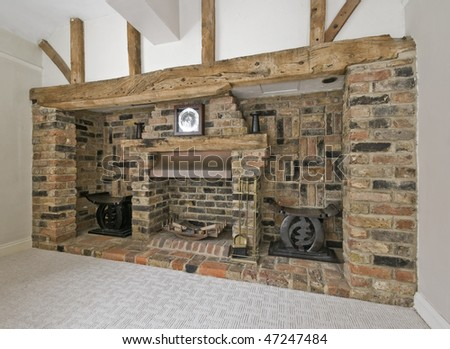 large fireplace with exposed brick and hard wood construction - stock photo