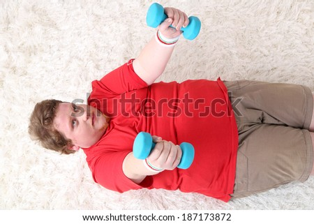 Large fitness man making exercises with dumbbells on floor, at home - stock photo