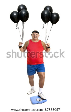 Large fitness man with weight scale and balloons isolated in white - stock photo