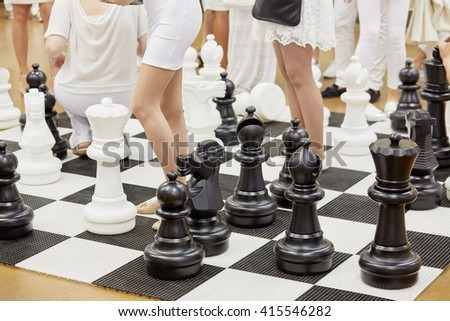 Large floor-stand chess figures and female legs among them. - stock photo