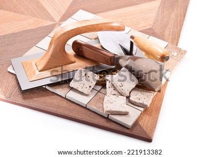 Large floor tiles, marble and decorative stone, trowel and spatula on a white background - stock photo