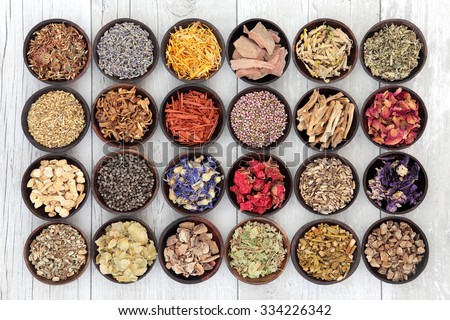 Large flower and herb selection used in herbal medicine over distressed white wooden  background. - stock photo