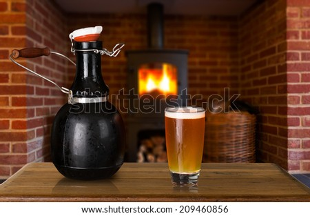 Large 64 fluid ounce four pint growler bottle with a glass of cold beer or ale in front of fire. Used by microbreweries to serve beer for home consumption - stock photo