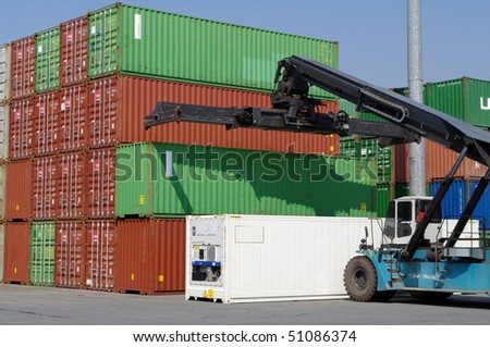 Large forklift stacking containers in port - stock photo