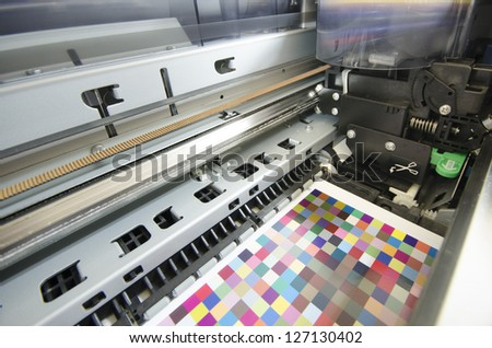 large format ink jet printer printing color managament target on paper roll - stock photo