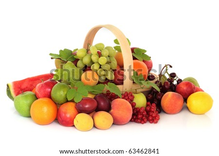 Large fruit collection in an arrangement with hop leaves around a rustic wooden basket, isolated over white background.