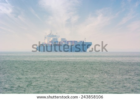 Large, fully-loaded, commercial container ship at anchor, just off the coast. - stock photo
