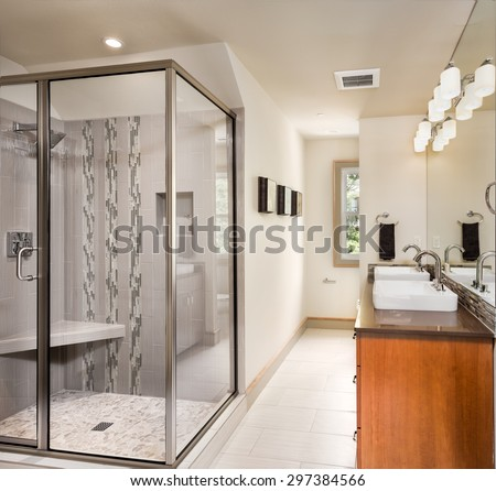 Large furnished bathroom in luxury home with tile floor, two sinks, fancy cabinets, large mirror, and shower - stock photo