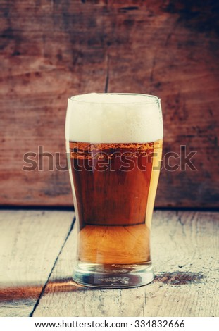 large glass of light beer with foam on the old wooden background, selective focus - stock photo