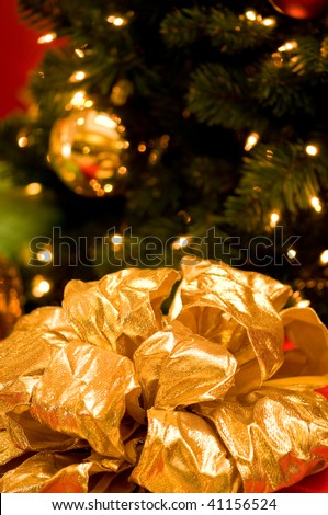 Large gold bow with Christmas tree in background - stock photo