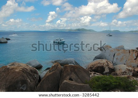 Large granite boulders, lush vegetation and boats at The Baths.  British Virgin Islands.