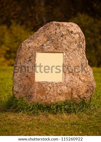Large granite stone with empty metal plate lying on a green grass - stock photo