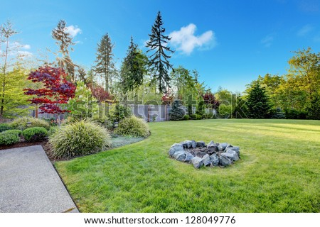 Large green backyard with beautiful landscape and fire pit. - stock photo