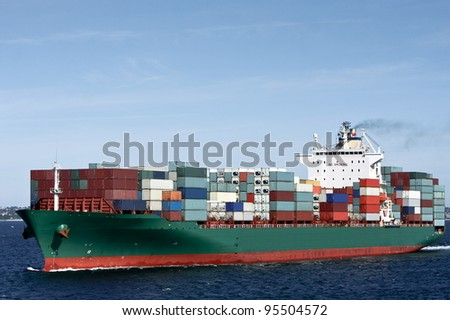 Large green container cargo ship at sea.