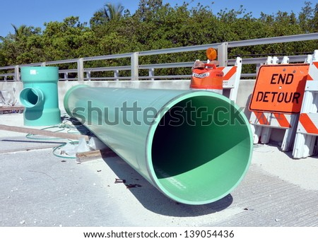 Large Green Industrial PVC Sewer Pipes At A Road Construction Site With Barricades And Detour Sign - stock photo