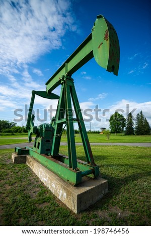 Large, green, old and rusting antique, decommissioned oil pumpjack, sometimes called a pump horse, or oil horse, on display.