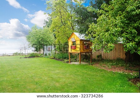 Large green spring grassy back yard with a view of the ocean and yellow kids tree house, play ground. - stock photo