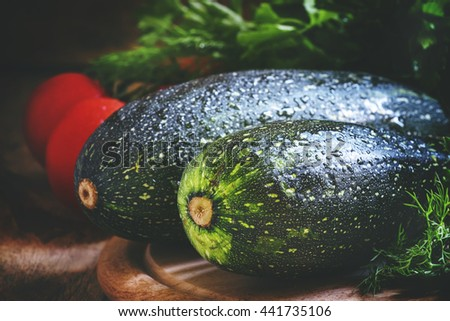 Large green zucchini, vintage wooden background, selective focus