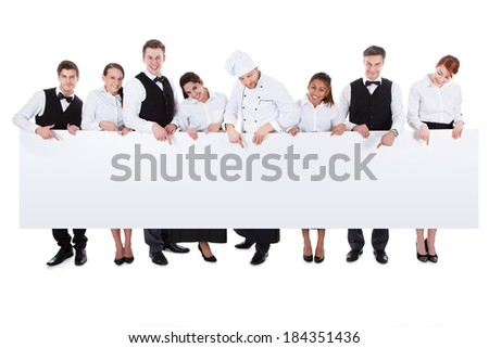 Large group of catering staff holding a blank banner with copyspace for your text including a chef  waiters  waitresses  hostess and wine steward  isolated on white - stock photo