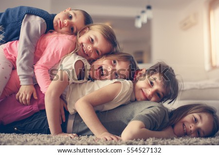 Large group of children lying at floor and having fun. Looking at camera.