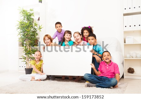 Large group of diversity looking kids, boys and girls sitting in the sofa in domestic room holding blank advertising cardboard. - stock photo