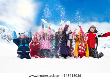 Large group of diversity looking kids boys and girls throwing snow in the air together - stock photo