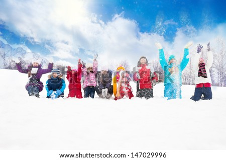 Large group of diversity looking kids boys and girls throwing snow in the air together sitting in a row - stock photo