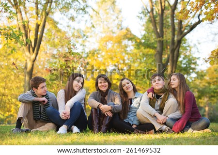 Large group of five teenagers with happy female teacher - stock photo