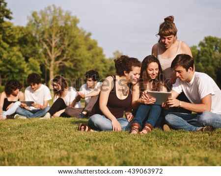 large group of friends tghether in a park studying on digital tablet, back to school