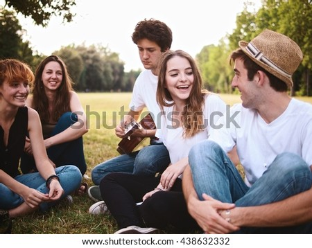 large group of friends together in a park having fun playing guitar and talking